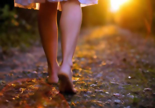 Imagem de Mulher caminhado de pés descalços numa rua de terra
